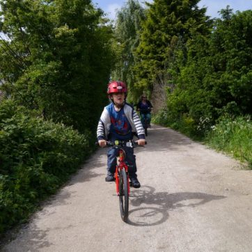 The eldest and other half riding along a gravel path