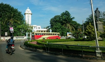 Bus goes round a roundabout outside the University of Kerala