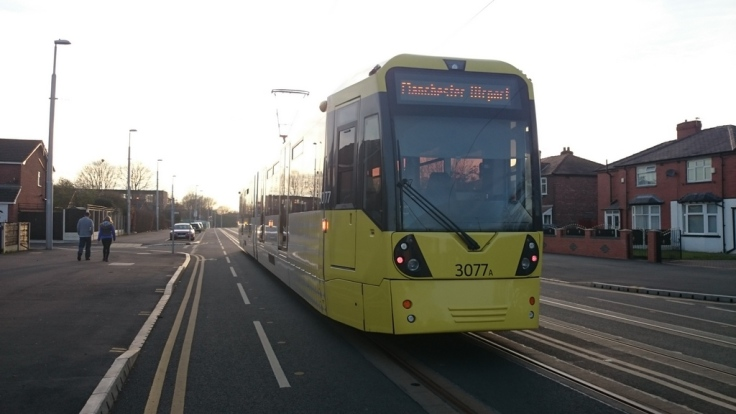 Metrolink tram going past the narrow painted line on Hardy Lane