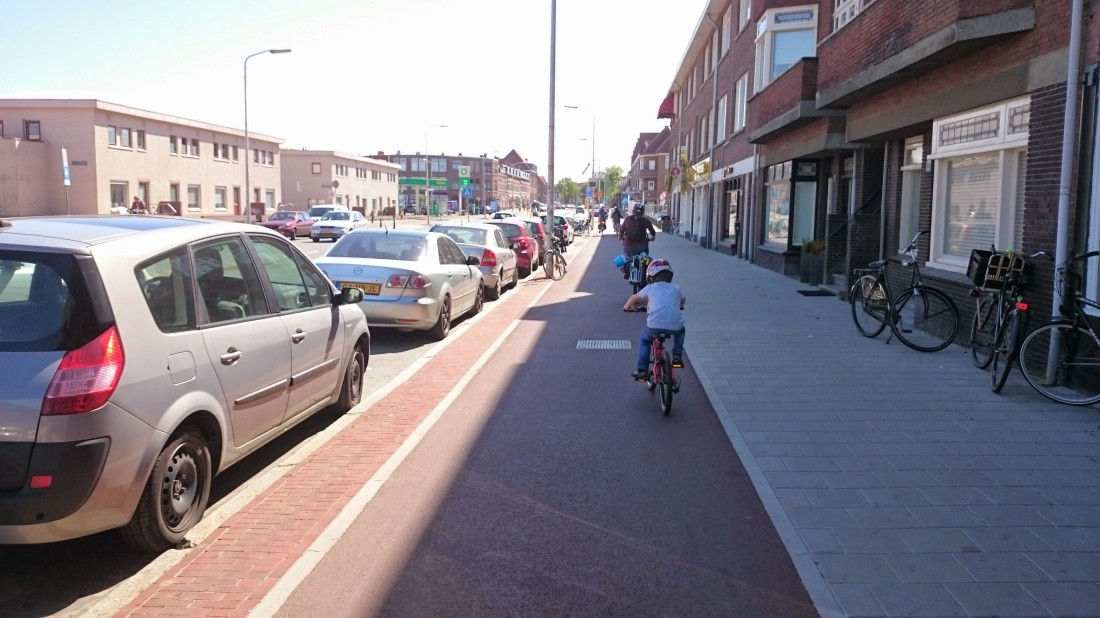 Typical distributor road with parking and segregated cycleway in The Netherlands